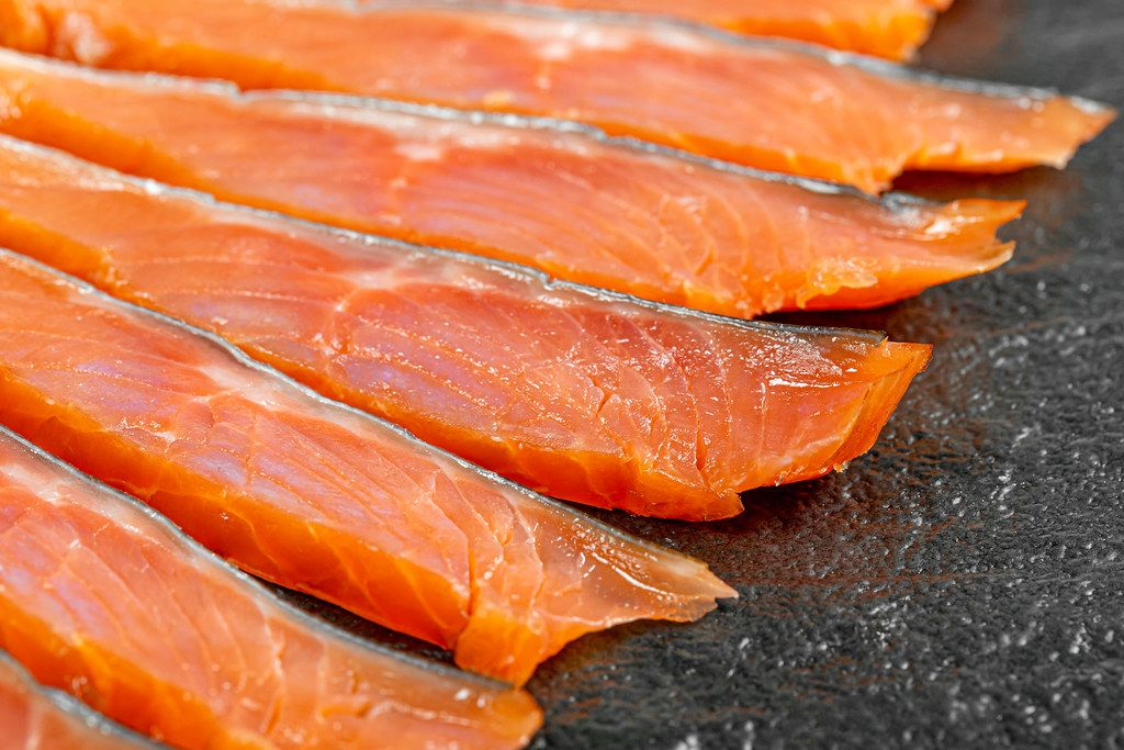 Sliced fillet of smoked red fish on a black background