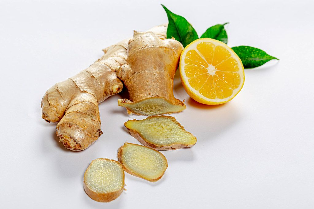 Sliced fresh ginger with lemon and green leaves