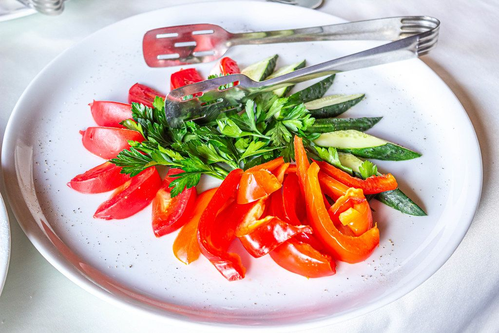 Sliced fresh tomatoes, cucumbers and bell peppers and parsley on a plate