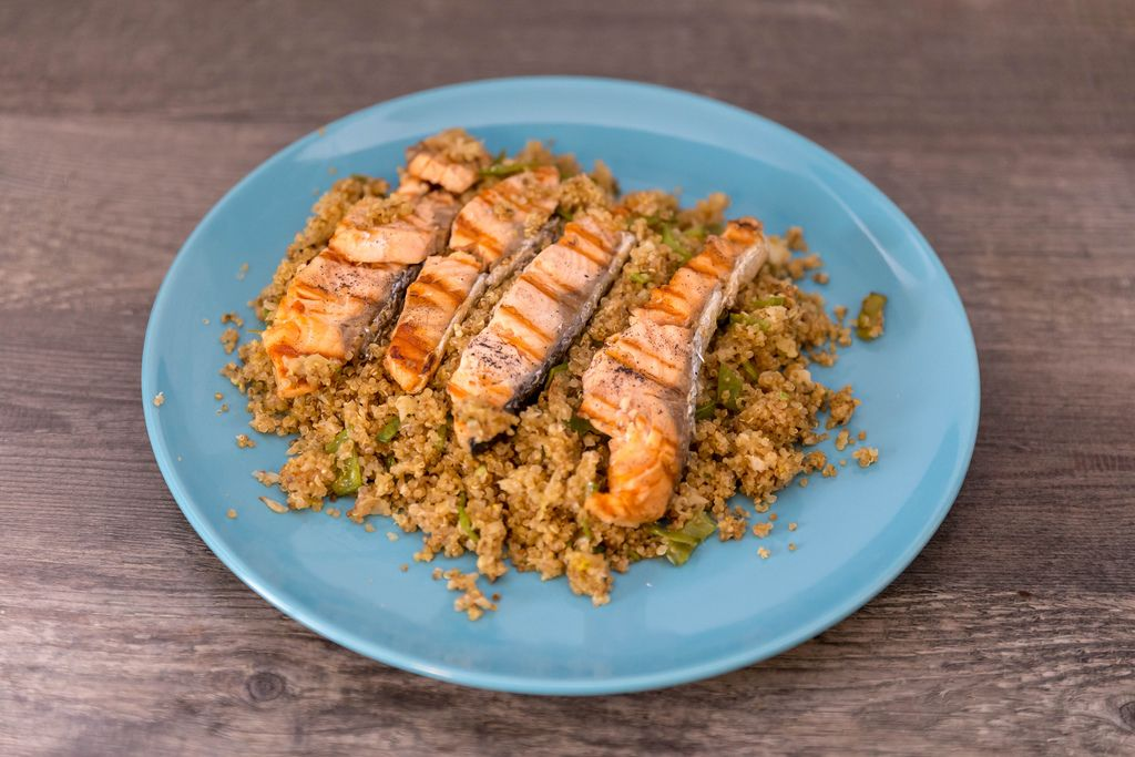 sliced, fried salmon with couscous on wooden table