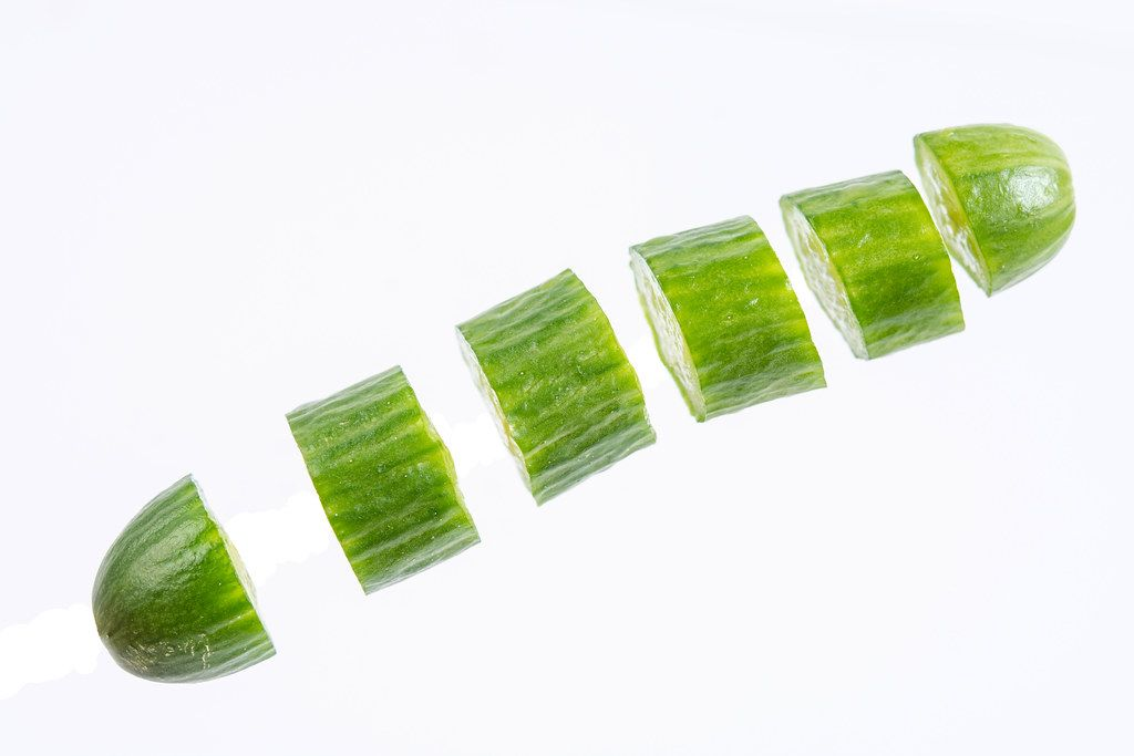 Sliced Mini Cucumber in the air above white background
