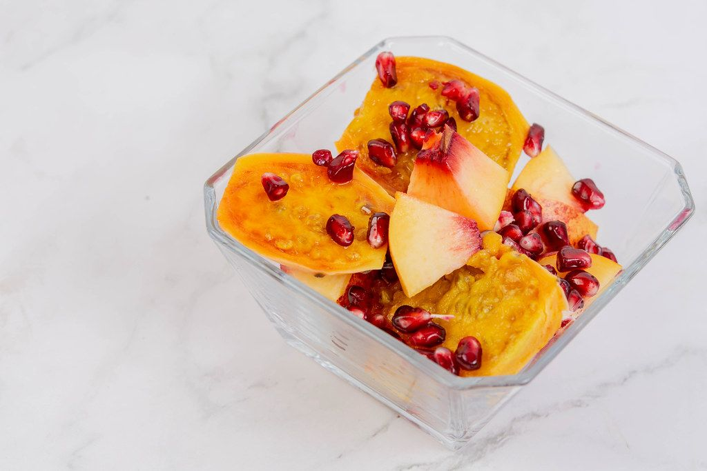 Sliced Peach with Pomegranate in the bowl