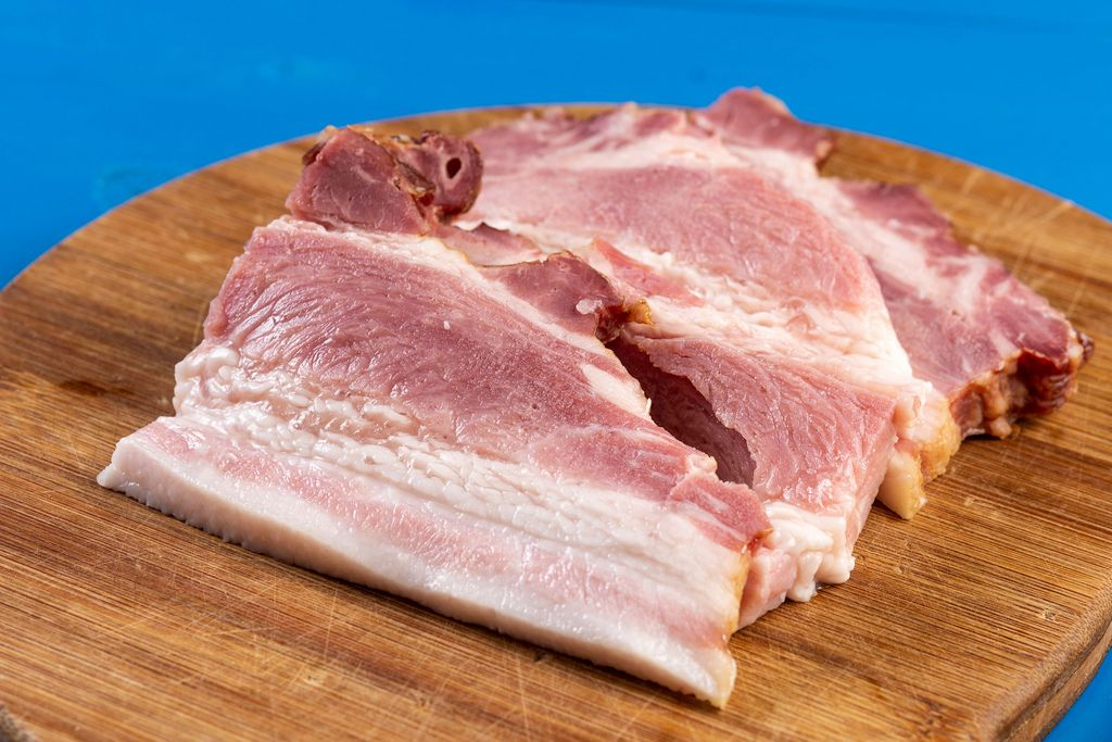Sliced Raw Bacon on the wooden board