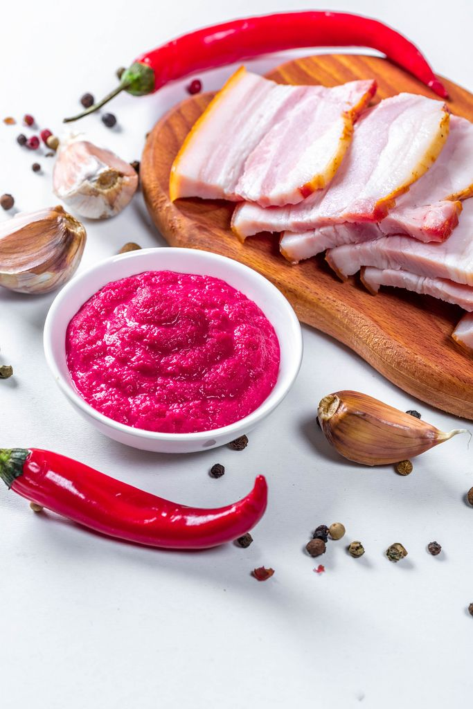 Sliced smoked bacon with horseradish sauce and spicy spices on white background