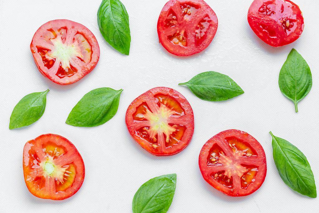 Sliced tomato and fresh Basil leaves on white background