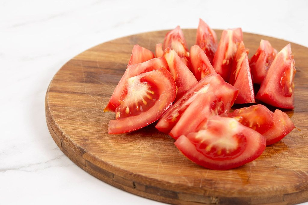 Sliced Tomato on the round cutting board
