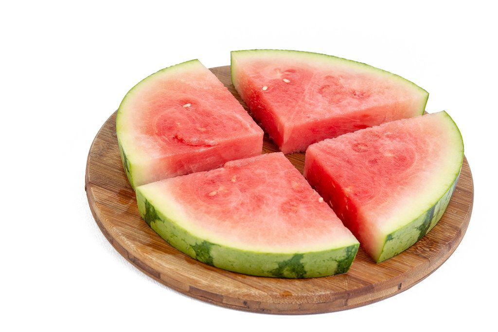 Sliced Watermelon arranged on the round wooden board