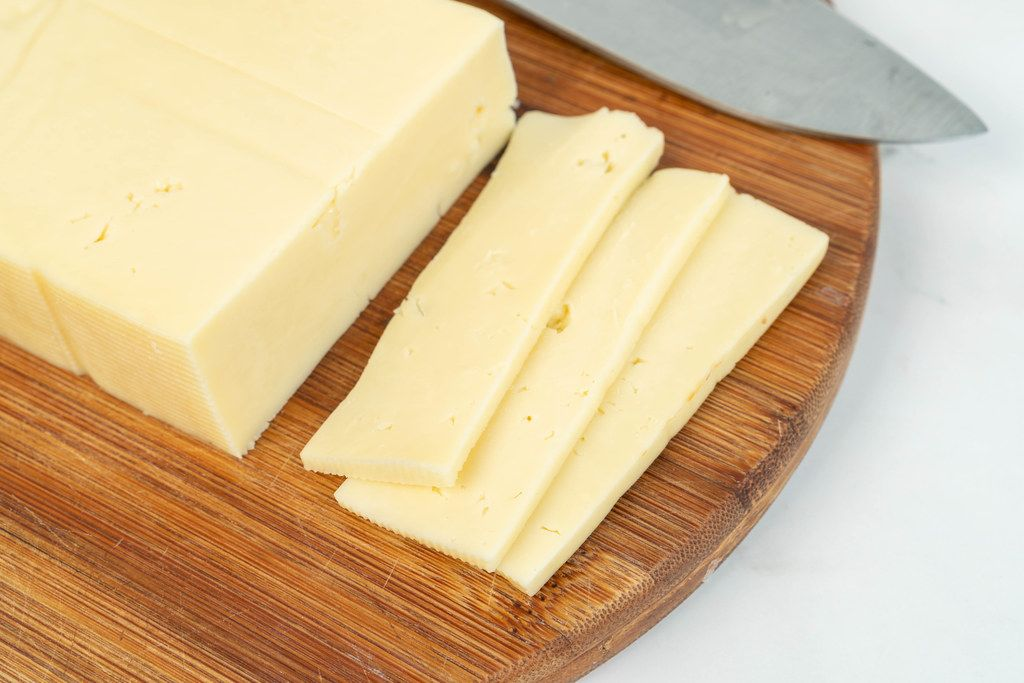 Sliced Yellow Cheese on the wooden cutting board (Flip 2019)