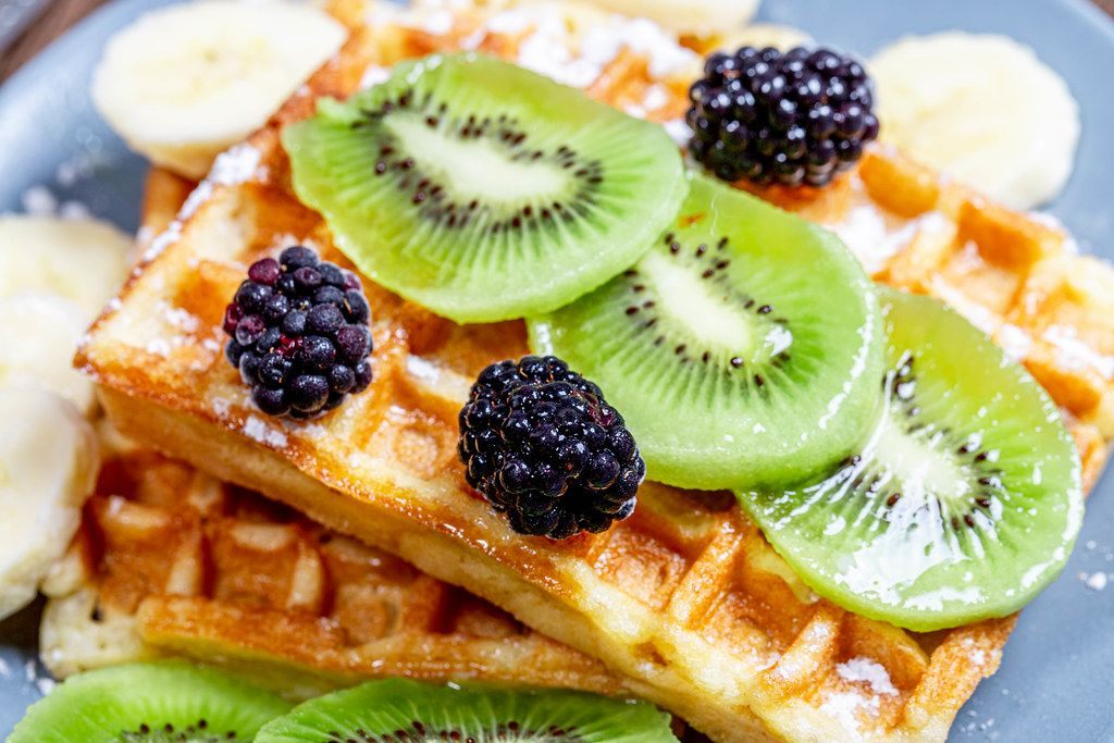Slices of kiwi and banana with mulberry on Belgian waffles close-up (Flip 2019)