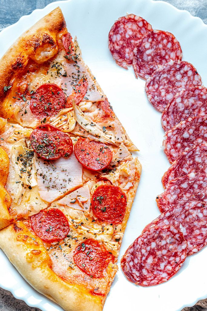 Slices of meat pizza with sliced smoked sausage on a white plate