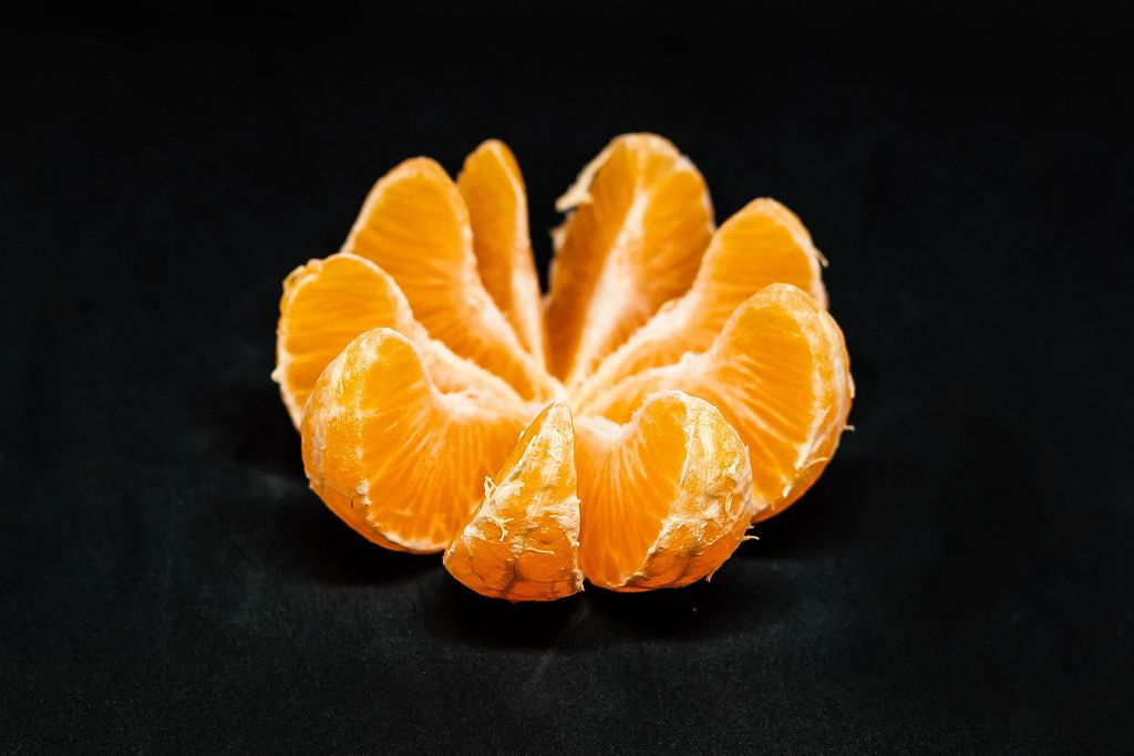 Slices Of Tangerine On Black Background