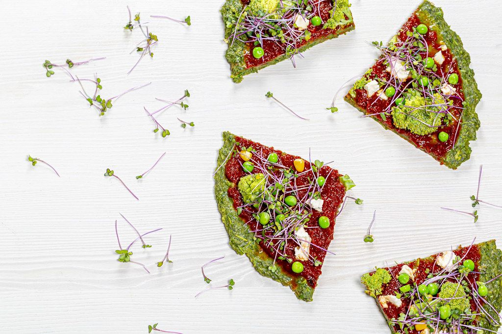Slices of vegetarian vegetable pizza with micro-green cabbage on a white wooden background. Top view