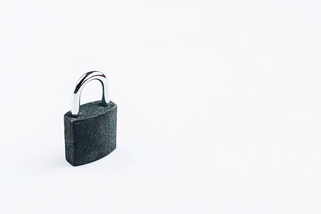 Small steel lock on white background