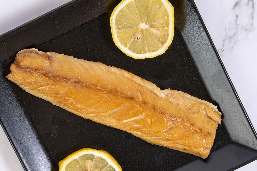 Smoked Mackerel fish with Lemon served on the plate
