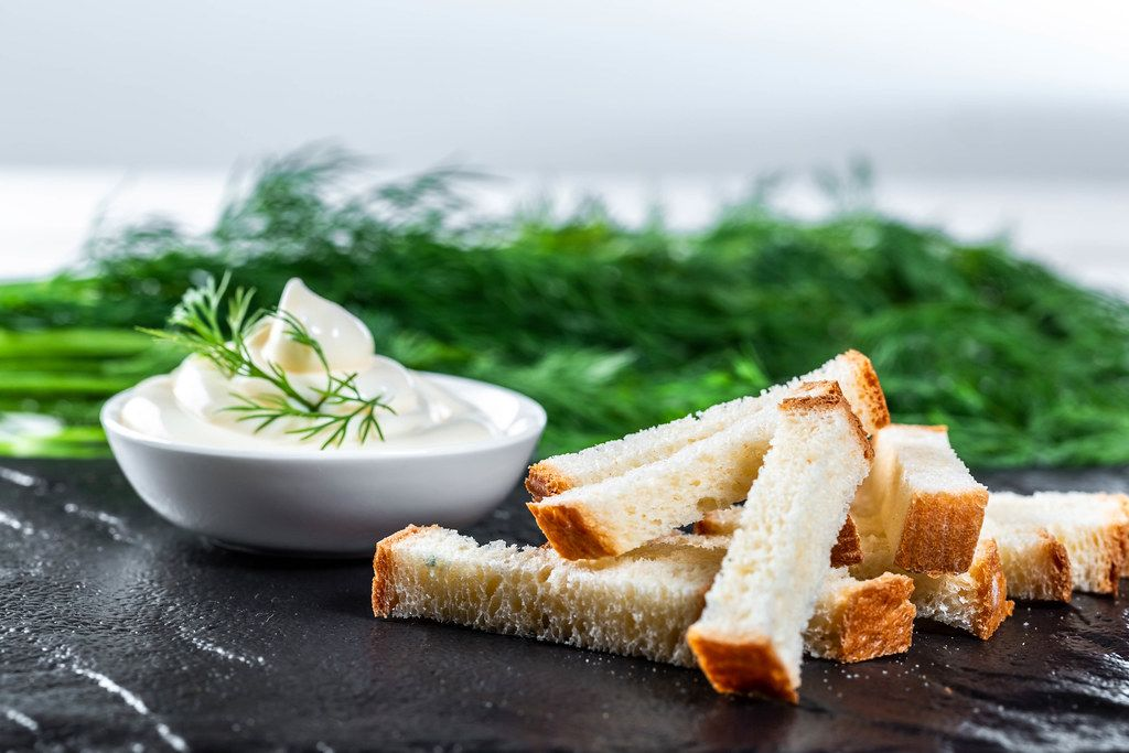 Snack aus Weißbrot mit Dip und Kräuter