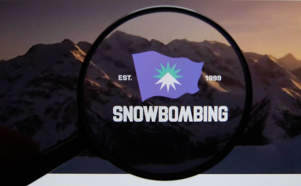 Snowbombing Festival logo on a computer screen with a magnifying glass