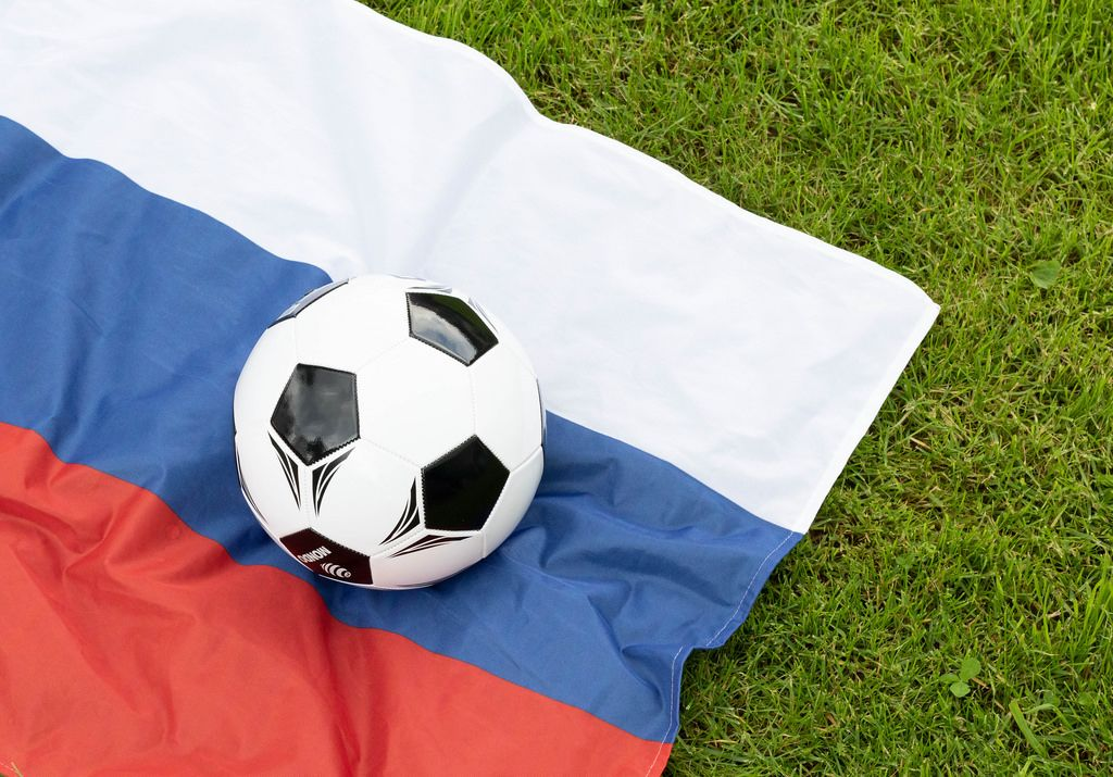 Soccer ball and Russian flag on green grass