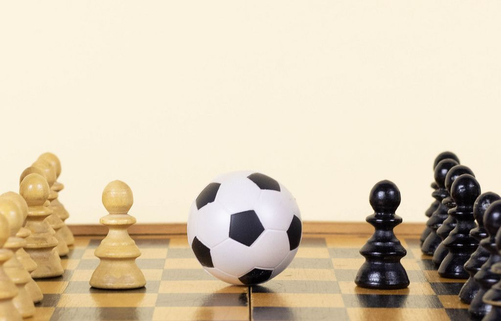 Soccer ball of chess pieces on the board