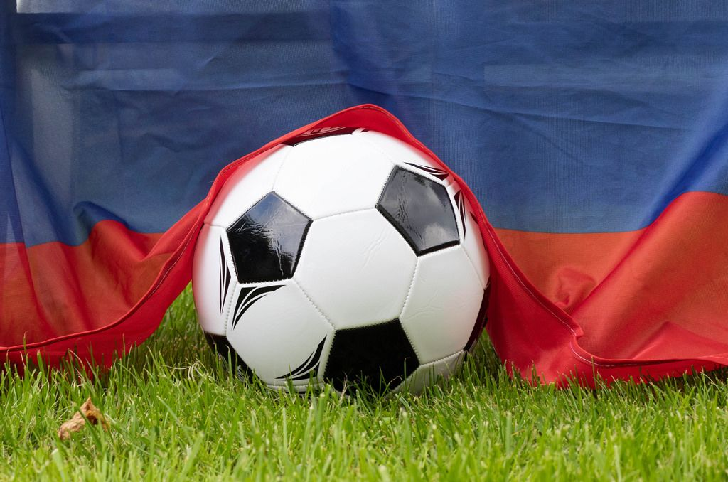 Soccer ball on grass covered with Russian flag