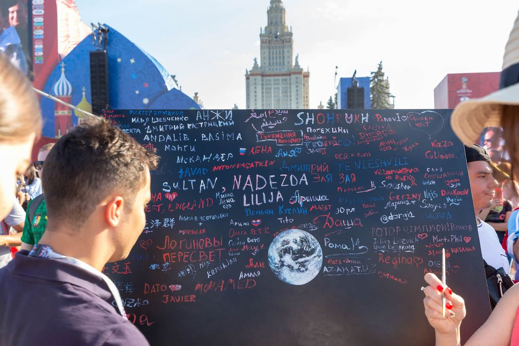 Soccer fans writing messages on black board at fan fest