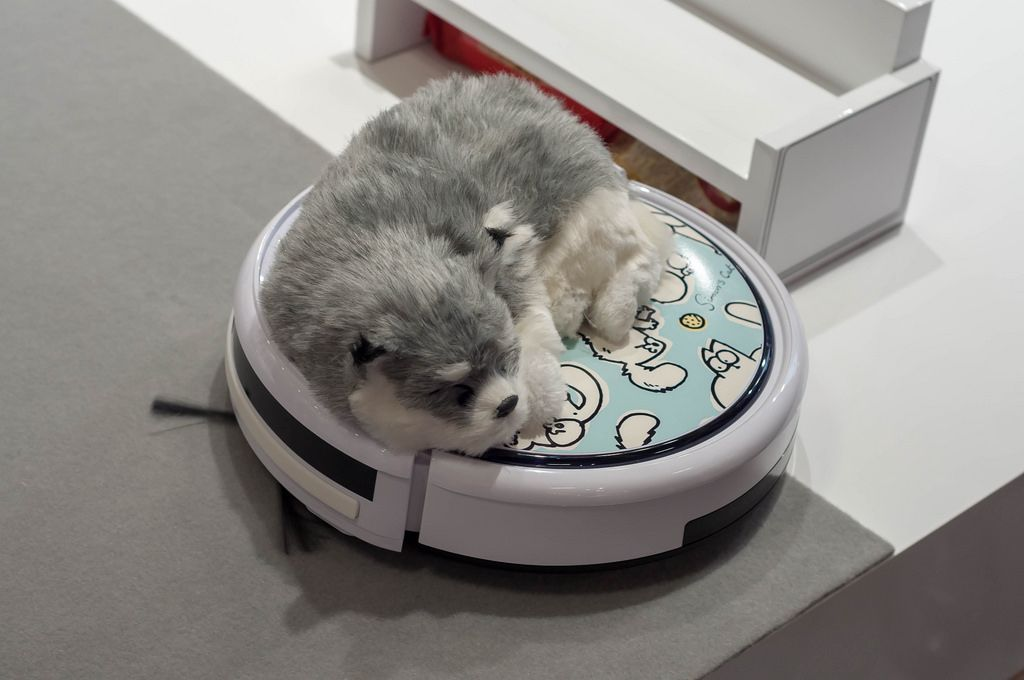 Soft toy dog on a robot vacuum cleaner with Simon's Cat cartoon