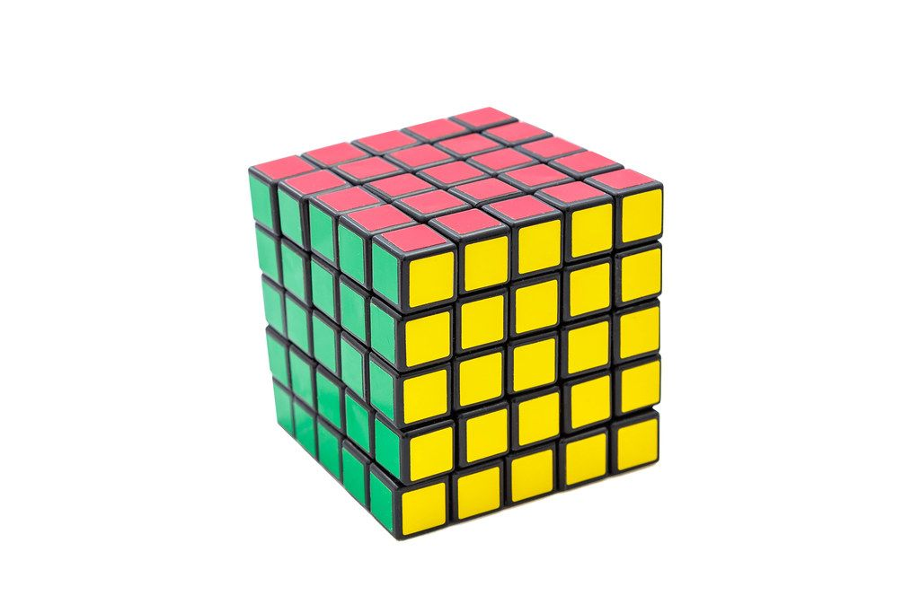 Solved Rubik's cube 5x5x5 on white background with green, yellow and red sides