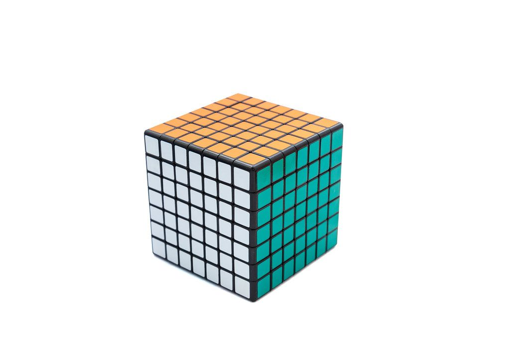 Solved Rubik's cube 7x7x7 on white background with green, white and orange sides (Flip 2019)