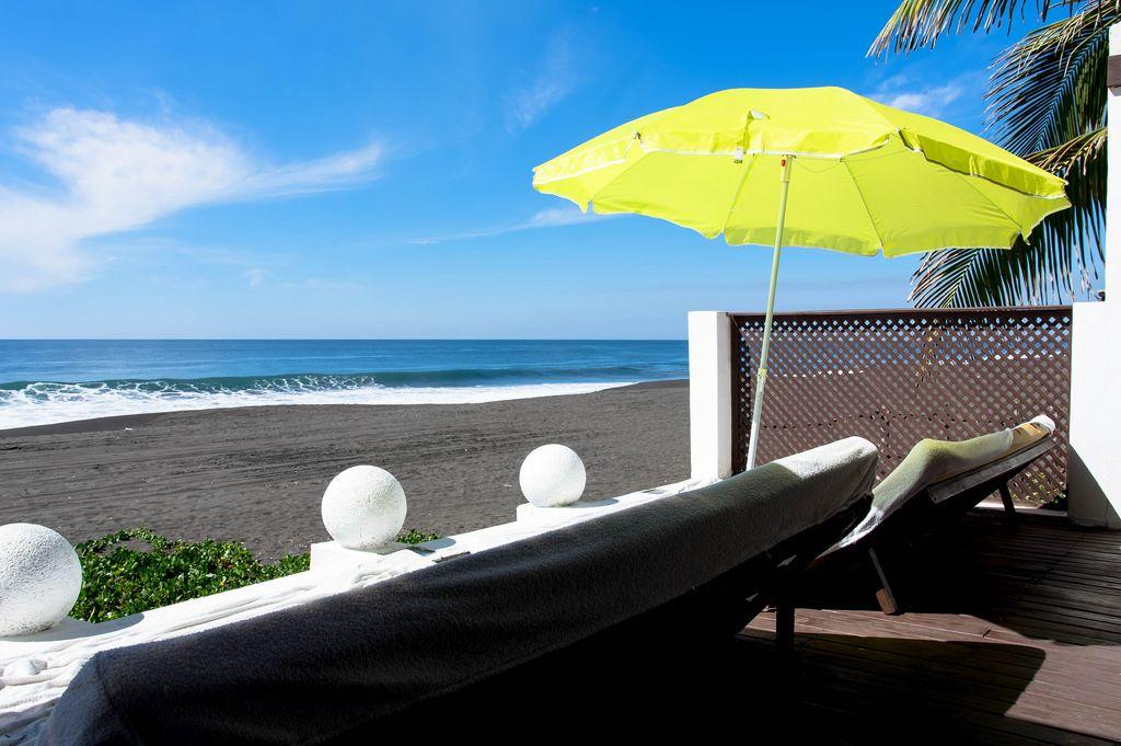 Sonnenbänke und grüner Sonnenschirm neben dem Strand