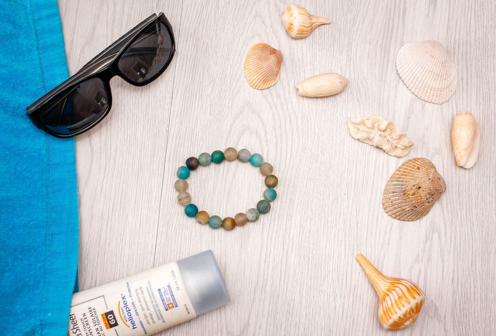 Sonnenbrille, Muscheln, Sonnencreme und Armband aus der Vogelperspektive