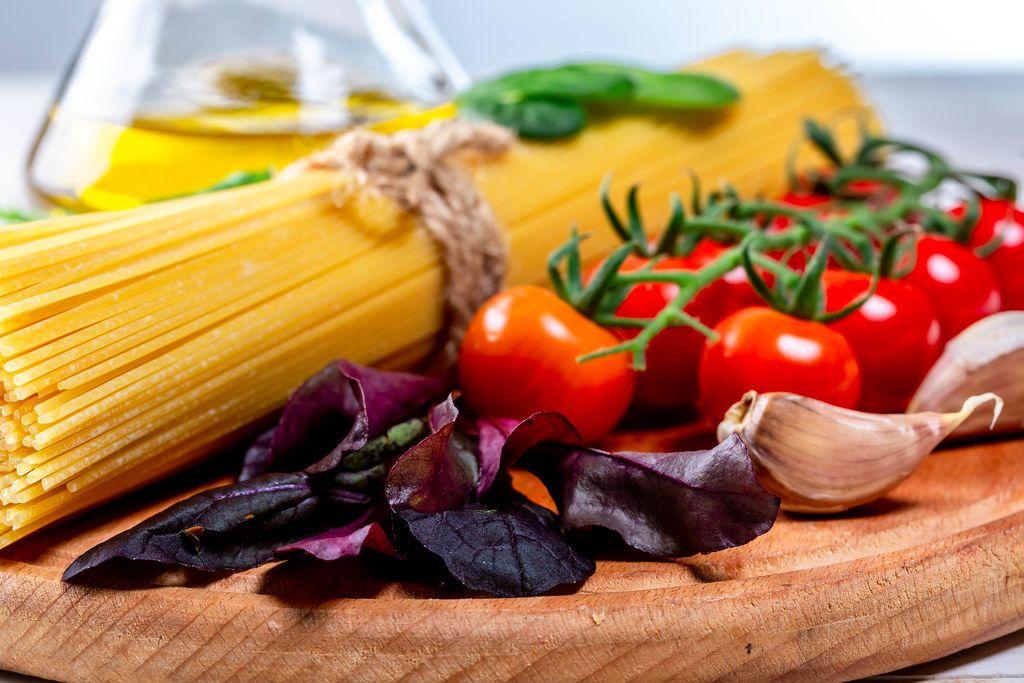 Spaghetti mit Tomaten, Knoblauch, Basilikum und Olivenöl auf einem runden Holzbrettchen