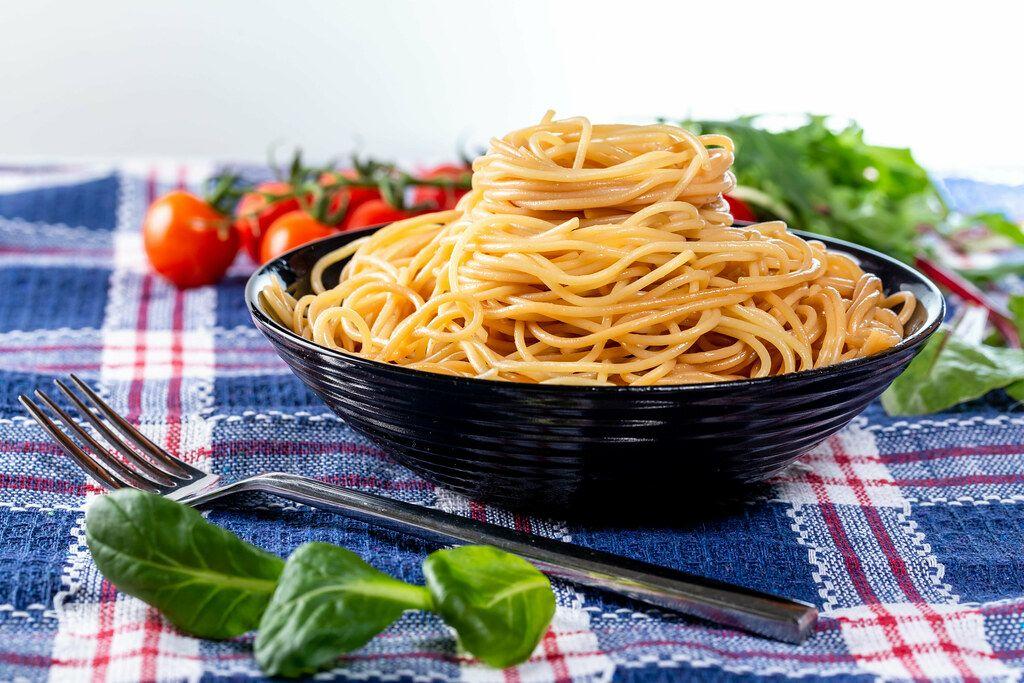Spaghetti-Nudeln in einer schwarzen Schale angerichtet, mit Basilikum-Kräuter und Tomaten auf einem blauen Geschirrtuch