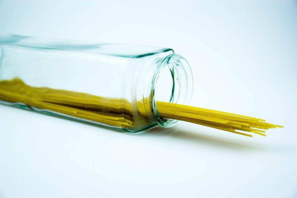 Spaghetti-Nudeln in eines Glas auf weißem Hintergrund