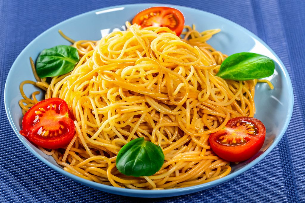 Spaghetti with tomatoes on a blue background