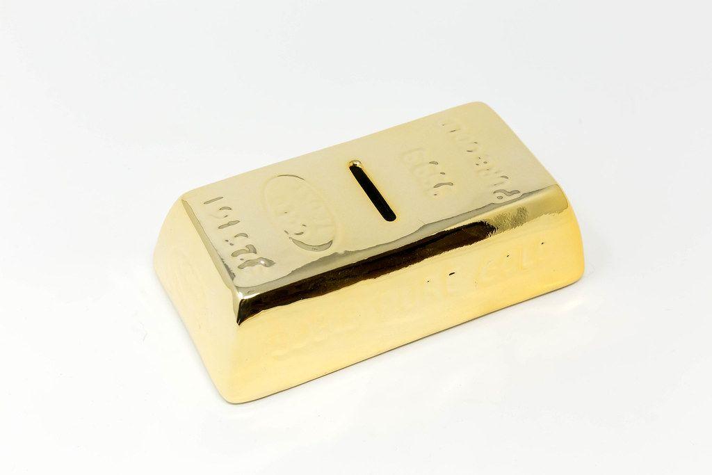 Spardose in Form von Goldbarren vor weißem Hintergrund