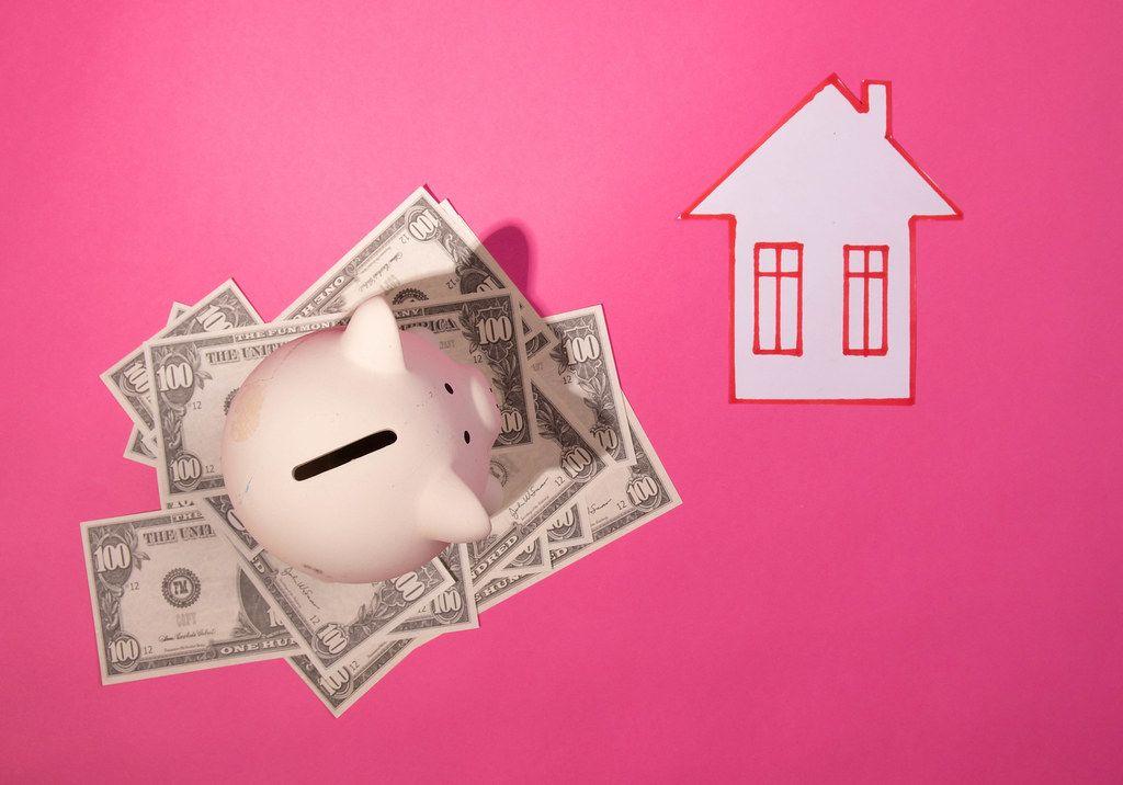 Sparschwein steht auf amerikanischen Geldscheinen, neben einem Haus aus Papier, vor pinke Hintergrund