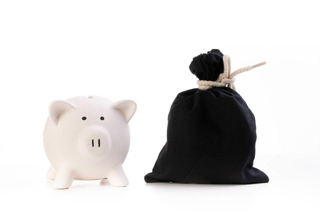 Sparschwein und schwarzer Geldsack vor weißem Hintergrund