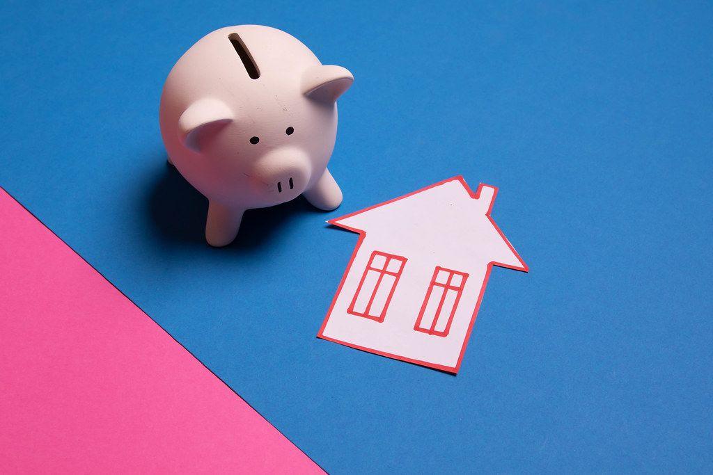 Sparschweinch neben einem gebastelten Haus aus Papier liegt auf blauem und pinke Untergrund