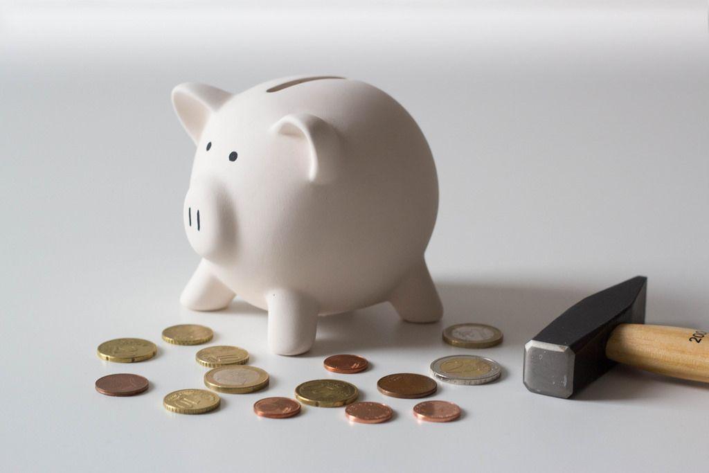 Sparschweinchen, Münzen und ein Hammer