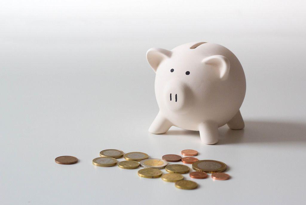 Sparschweinchen und Münzen auf einem weißen Tisch