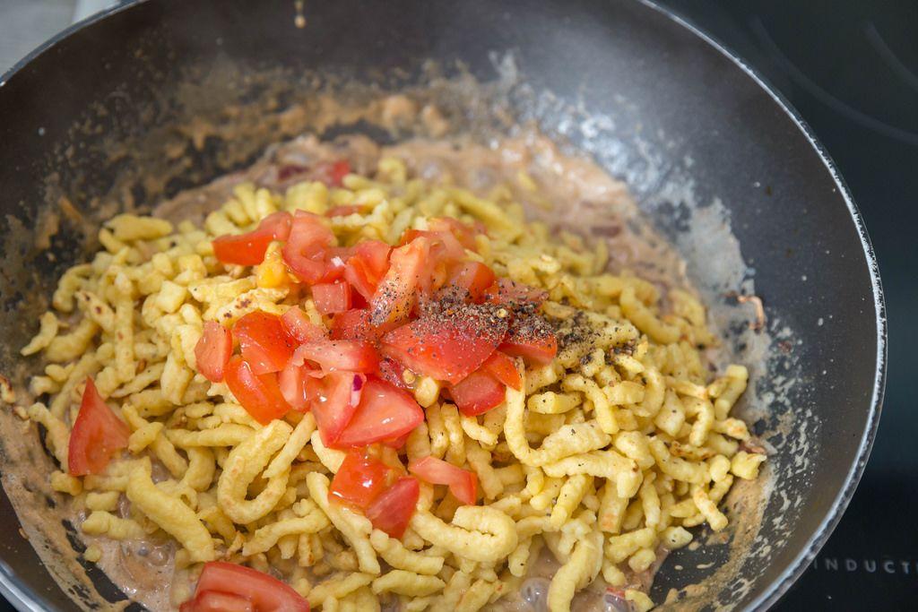 Spätzle mit cremiger Soße und Tomaten werden im Wok zubereitet