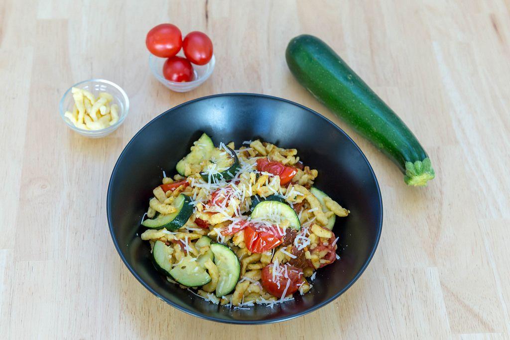 Spätzle mit getrockneten Tomaten und Zucchini mit Zutaten im Hintergrund