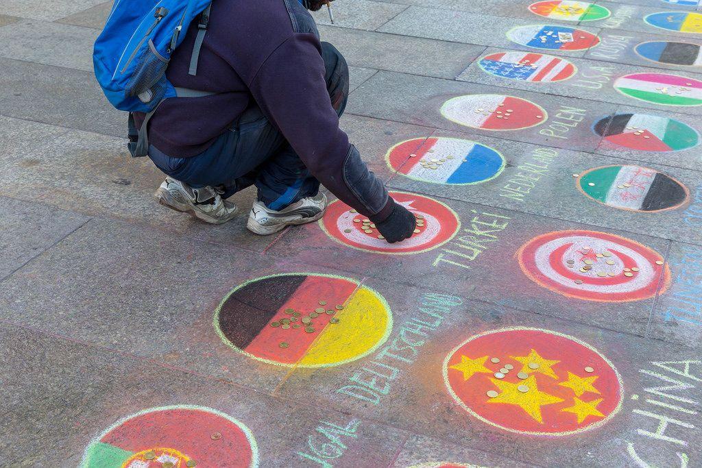 Spendenaktion - Ein Mann legt eine Münze auf eine aus Kreide gemalte Flagge auf dem Platz vor dem Kölner Dom