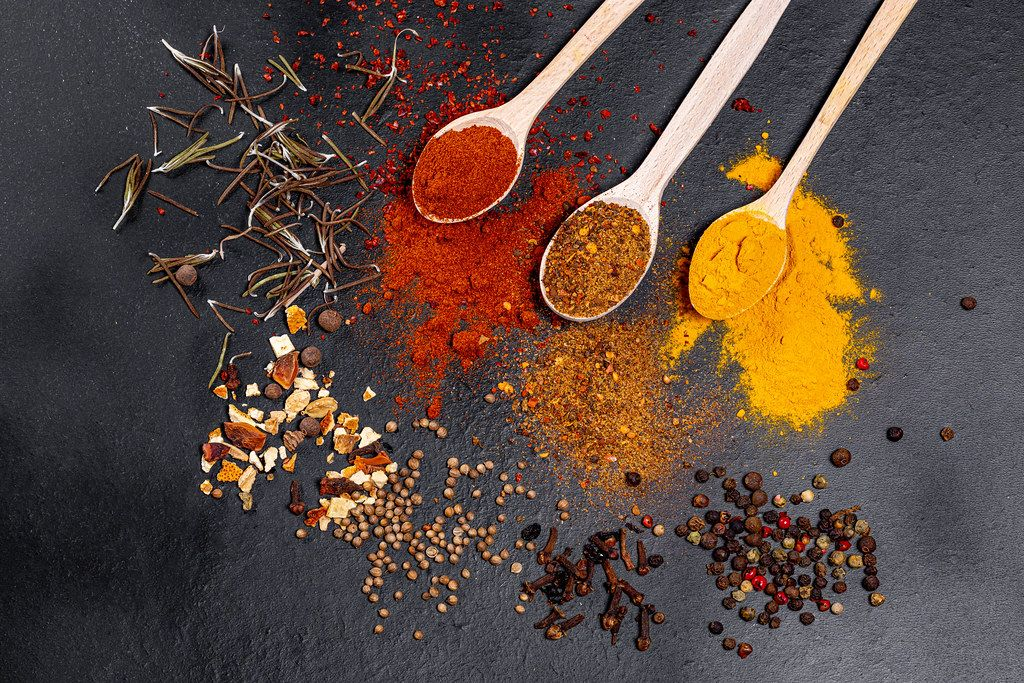 Spices in wooden spoons and scattered on a black background. Top view