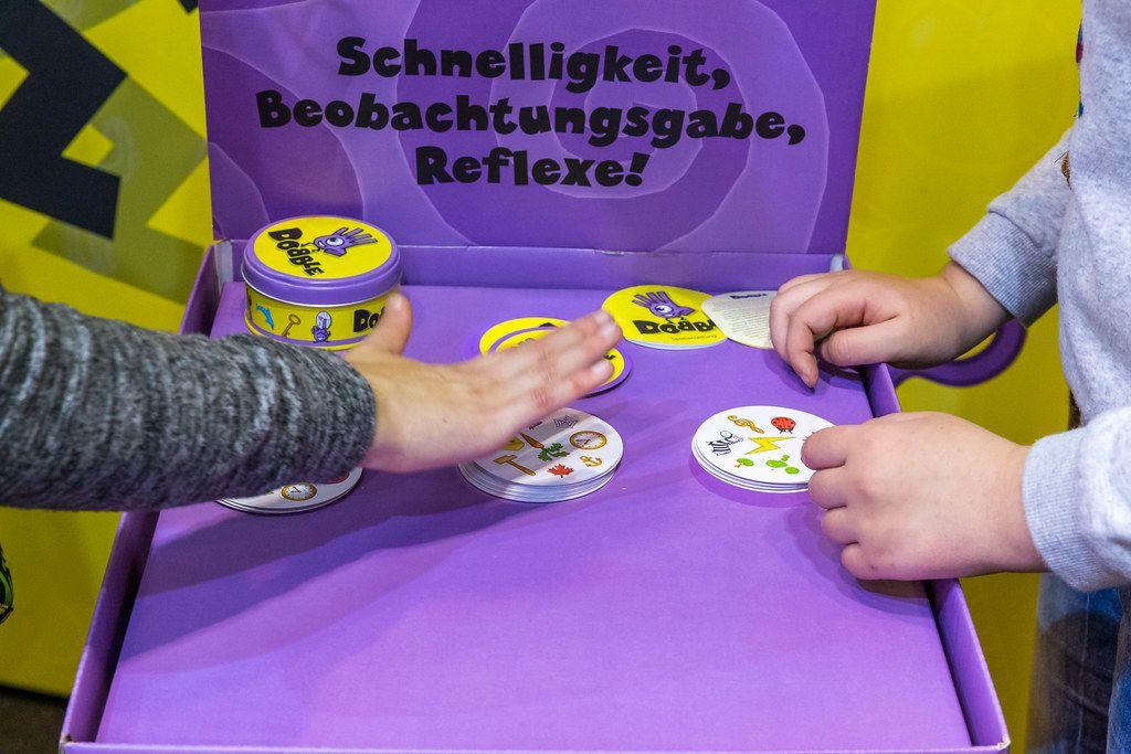SPIEL 19 in Essen: zwei Besucher spielen Beobachtungs- und Reaktionsspiel