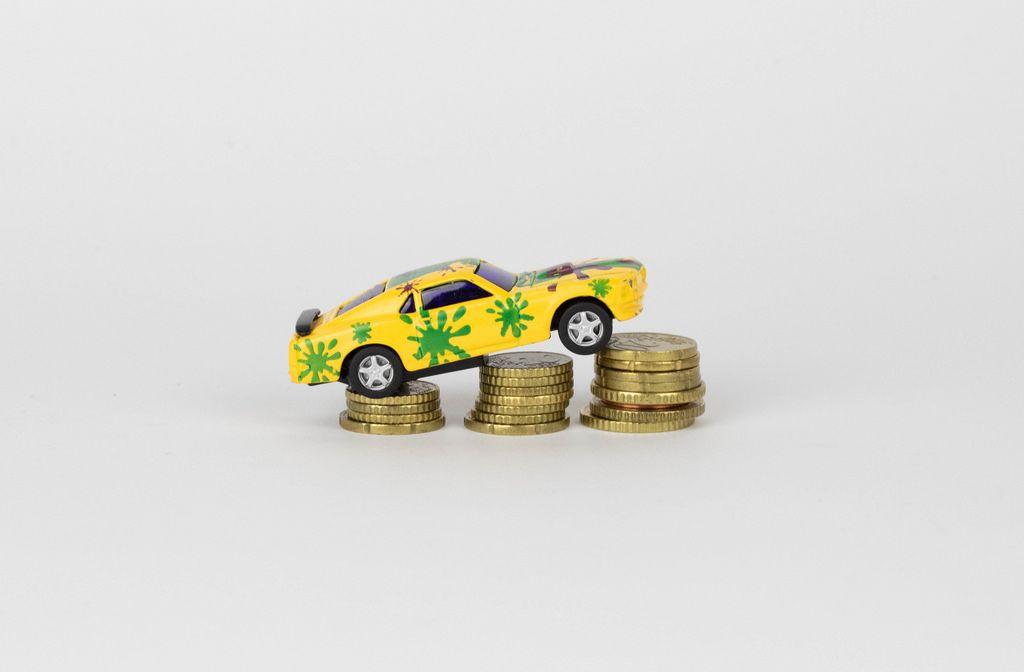 Spielzeugauto auf aufeinander gestapelten Münzen