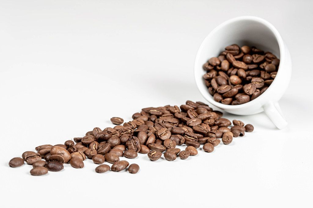 Spilled coffee beans from the white ceramic cup on white background
