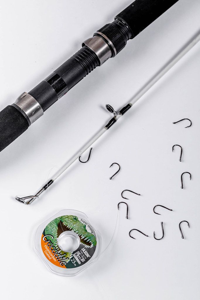 Spinning, hooks and fishing line on white background
