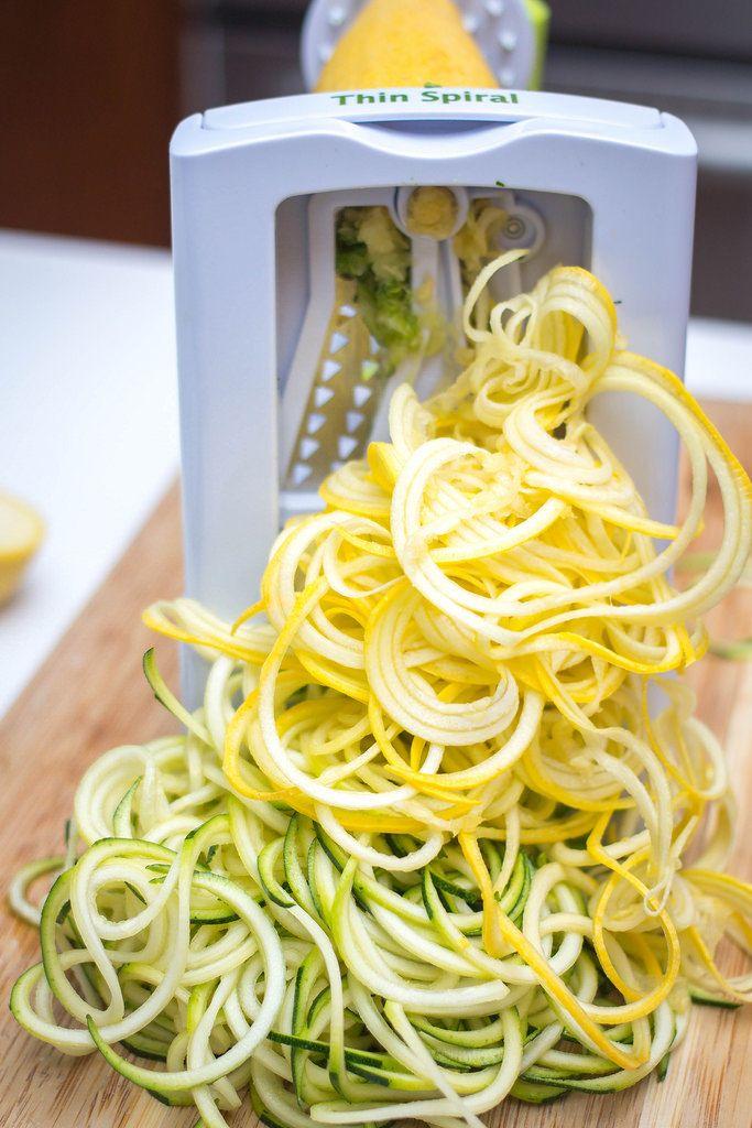 Spirulizer Küchengerät mit dünn geschnittenen Gemüsestreifen aus gelber und grüner Zucchini auf Holzbrett