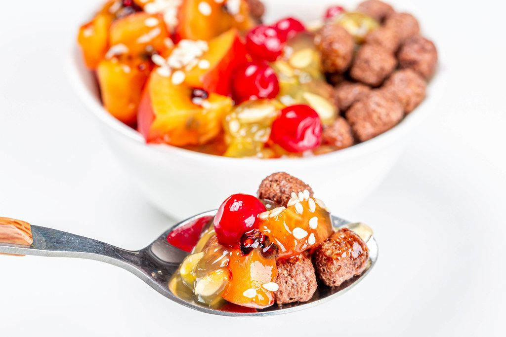 Spoon with chocolate corn balls and fruit slices