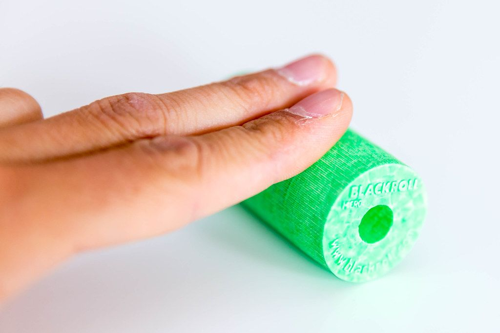 Sportsman puts two finger on the Blackroll's green fascia roll, on a white surface, to release tensions and to strengthen his hand muscles